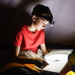 Chłopiec czytający książkę przy latarce