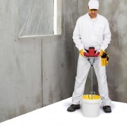 malarz miesza farbę do ściany